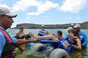 Pessoal treinado pela EcoNoronha acompanha cadeirante no mar