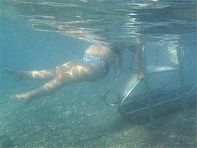 Matoula Kastrioti, que sofre de esclerose múltipla, entra no mar em praia em Alepochori