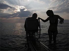 Lefteris Theofilou, que sofre de paraplegia, com a mulher, Eleni, com paralisia cerebral
