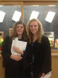 Carly (à esq) junto com Mia, a oradora da turma, na formatura de ambas do segundo grau