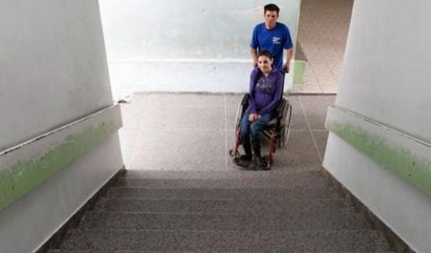 Moça em cadeira de rodas na frente de uma escada