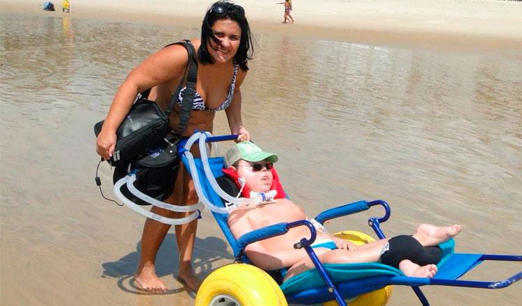 Fátima empurra Lucas em um carrinho no mar