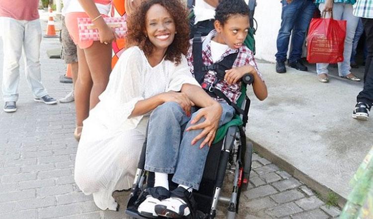 Isabel Filardis ajoelhada ao lado do filho na cadeira de rodas