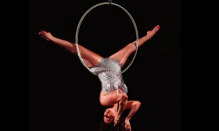 Mulher faz movimento acrobático em um arco