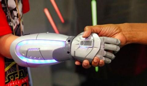 Braço biônico em forma de sabre de luz apertando a mão de uma pessoa