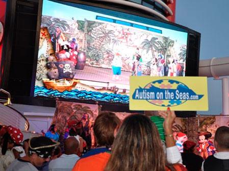 Várias crianças de costas para a foto assistindo a um filme em uma tela de cinema