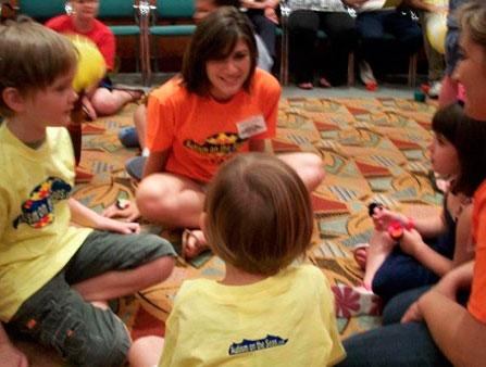 Uma profissional de camisa laranja brinca com três crianças