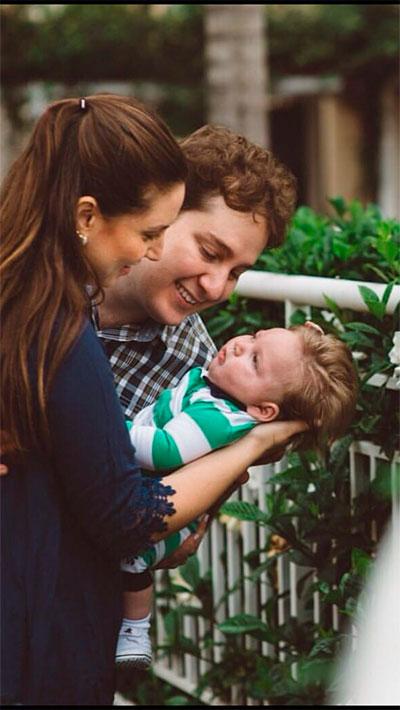 Mulher segura bebê no colo ao lado de um homem em um jardim