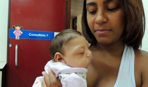 Mãe segurando seu bebê no colo na porta de um consultório médico