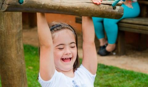 Garotinha com deficiência brinca, pendurando-se em uma árvore