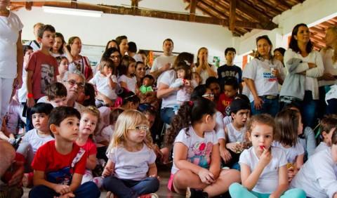 Crianças de várias idades sentadas no chão ou no colo de adultos