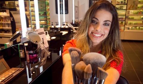 Jovem sorrindo em uma mesa de maquiagem e segurando vários pinceis