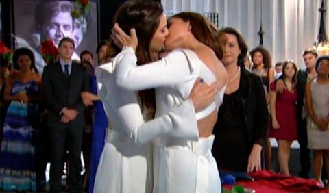 Duas mulheres vestidas de noiva se beijam