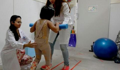 Duas profissionais de saúde, uma ajoelhada e outra em pé, ajudando uma criança a andar utilizando aparelho ortopédico, em uma clínica