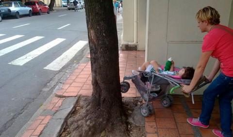 Mulher tentando passar por uma calçada com uma árvore no centro, empurrando um carrinho de criança