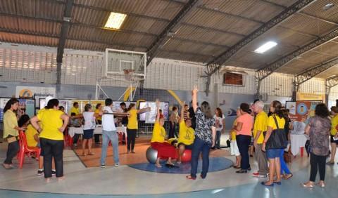 Várias pessoas, entre homens e mulheres de várias idades, realizam exercícios físicos em um ginásio