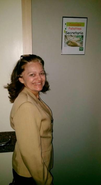 Mulher de meia idade, de perfil, sorrindo, em frente a uma parede