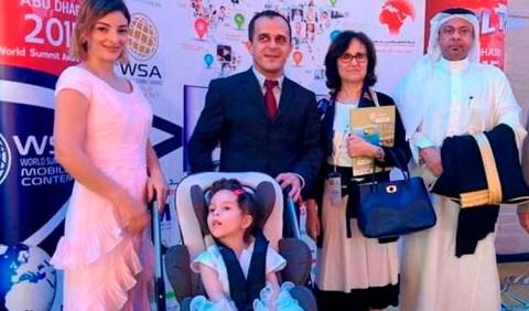 Cinco pessoas posicionadas, uma ao lado da outra, de frente: uma mulher de vestido salmão, uma garotinha em um carrinho infantil, um homem de paletó, uma mulher em roupa executiva e um homem em trajes árabes