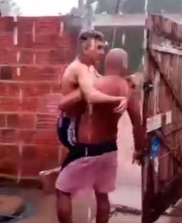 Homem carrega um rapaz no colo debaixo da chuva