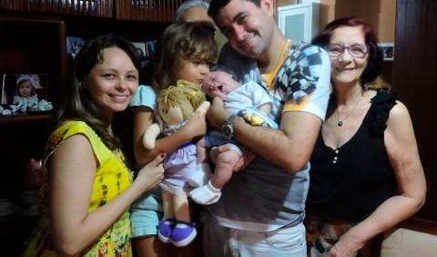 Cinco pessoas de frente a uma estante: uma mulher à esquerda, segurando uma garotinha no colo, um homem com um bebê nos braços e uma senhora à direita