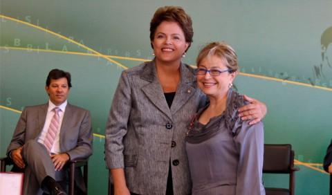 Duas mulheres em primeira plano abraçadas, a presidenta Dilma à esquerda e a professora Maria Teresa, e o prefeito de São Paulo, Fernando Haddad, sentado, ao fundo, do lado esquerdo