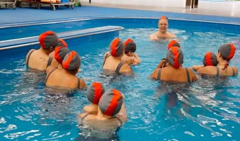 Seis mulheres seguram seis crianças em uma piscina, orientadas por uma professora