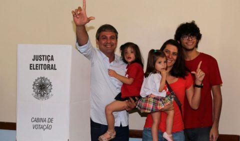 Homem saindo da cabine de votação, fazendo um gesto de um L com os dedos, segurando uma menina no colo e ao lado de uma mulher, fazendo o mesmo gesto, com outra garotinha no colo e um rapaz ao lado dela