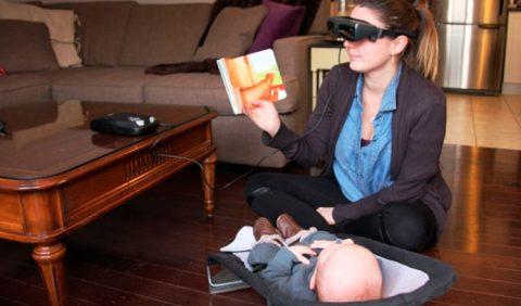 Mulher sentada no chão, usando um óculos especial, segura um livro que lê para seu bebê, deitado a sua frente. Ao fundo, um sofá e uma mesinha
