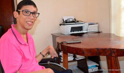 Rapaz de óculos e blusa cor de rosa, em uma cadeira de rodas, sorrindo para a câmera