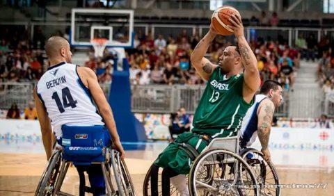 Jogador brasileiro de basquete em cadeira de rodas, de uniforme verde, ergue a bola de basquete, sendo observado pelo adversário, de uniforme branco.