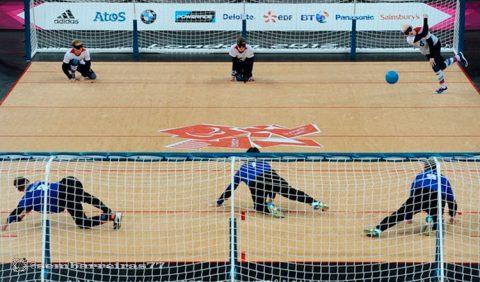 Quadra de goalball, com dois times. Embaixo, três jogadores de uniforme azul, e, em cima, três de uniforme branco com um deles arremessando a bola no canto superior direito