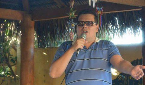 Rapaz jovem, de óculos escuros e blusa azul, cantando com um microfone na mão