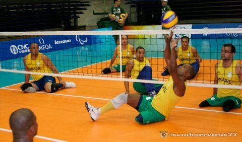 Treino da seleção brasileira de vôlei sentado com cinco jogadores de um lado da rede e dois do outro lado, com um deles fazendo o movimento de levantamento da bola
