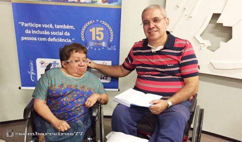 Duas pessoas, um homem e uma mulher, sentadas em cadeiras de rodas. Ele segura um livro aberto no colo. Atrás dela, um banner azul vertical