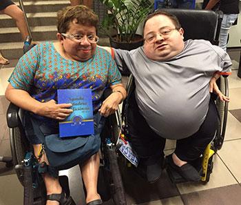 Casal de cadeirantes, um ao lado do outro. À esquerda, uma mulher segurando um livro de capa azul, e, à direita, um rapaz com o braço direito no ombro da mulher