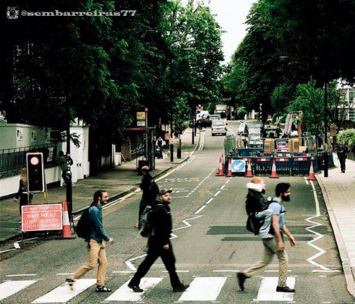 Três rapazes atravessam uma rua, relativamente vazia, um atrás do outro. O da frente carrega, nas costas, uma mochila com um quarto rapaz sentado nela. No entorno da foto, muitas árvores, e, ao fundo, uma obra