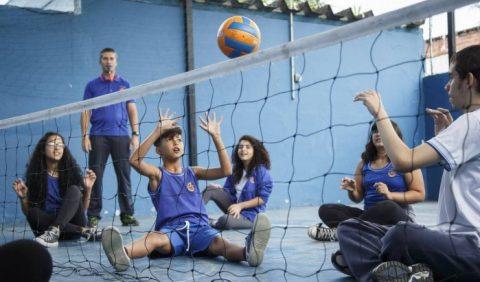 Uma quadra de vôlei sentado. Um garoto joga bola com um homem, de frente pra ele, enquanto três meninas e um homem, em pé, observam a atividade.