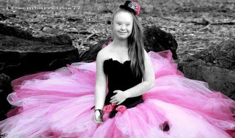 Garota com Síndrome de Down, sorrindo, sentada na areia de uma praia, vestindo uma longa saia rodada cor de rosa e um bustiê preto. Ao fundo, a água do mar.