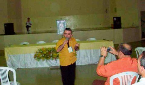 Rapaz em pé, segurando microfone, de frente pra foto, palestrando. Atrás dele, uma grande mesa coberta por uma toalha amarela. A sua frente, do lado direito, um homem sentado o filma com um celular