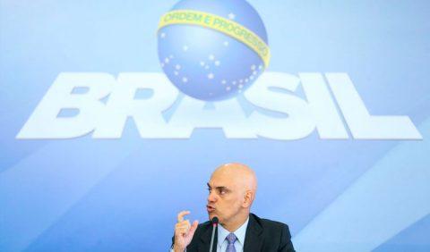 Homem careca, de paletó, discursando ao microfone e, ao fundo, uma tela azul claro com o símbolo do governo, o nome Brasil e uma bola azul ao centro