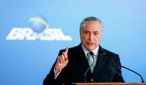 Presidente Michel Temer discursando ao microfone e, ao fundo, uma tela azul claro com o símbolo do seu governo, o nome Brasil e uma bola azul ao centro