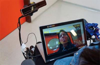 Imagem de um tela em terceira dimensão, acoplada em uma cadeira de rodas, que capta os sinais faciais do usuário e interpreta como ordens de movimento. No centro da tela, o rosto de uma mulher e várias marcações em amarelo