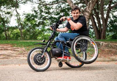 Foto em um parque de um homem em uma cadeira de rodas especial, composta por motor elétrico, guidão e uma roda na frente