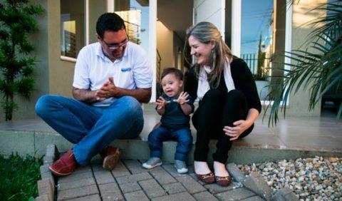 Homem e mulher brincam com um garotinho com Síndrome de Down, sentados no batente da varanda de casa