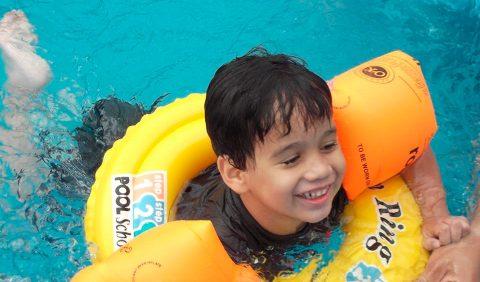 Garotinho sorrindo, em uma piscina, com boias nos braços e uma redonda, no peito