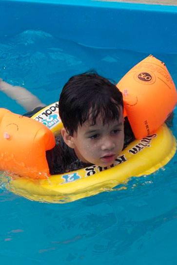 Garotinho em uma piscina, com boias nos braços e uma redonda, no peito