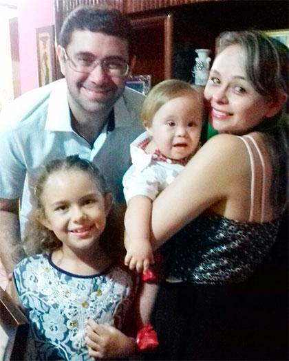 Foto vertical de quatro pessoas sorrindo. Um homem de óculos, uma garotinha a sua frente e uma mulher à direita com um bebê no colo