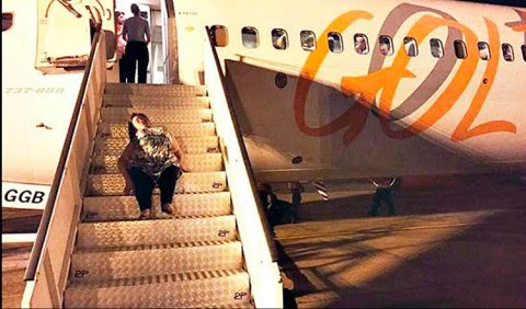 Mulher deficiente sobe a rampa de um avião da GOL, se arrastando