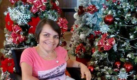 Mulher em cadeira de rodas, sorrindo, ao lado de uma árvore de Natal