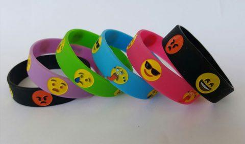 Seis braceletes, nas cores preta, lilás, verde, azul, vermelha e preta novamente. Cada um deles tem o desenho de um rostinho amarelo e vermelho, representando uma emoção diferente
